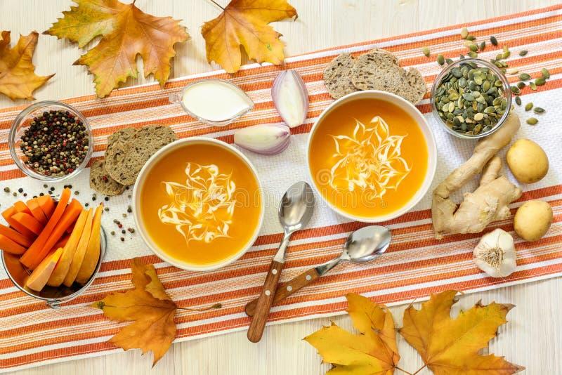 Dos cuencos de puré y de ingredientes, hojas de arce, visión superior de la sopa de la calabaza foto de archivo