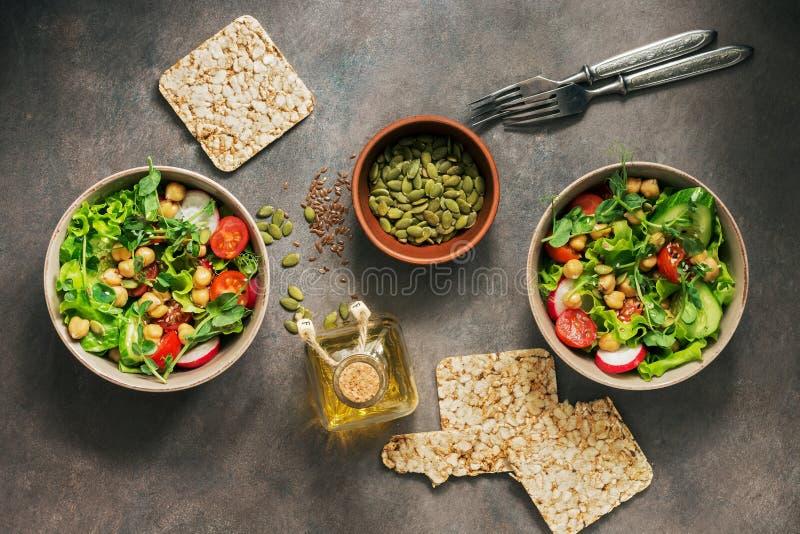 Dos cuencos de vegano y de ensalada dietética vegetariana de verduras frescas, de garbanzos y de semillas en un fondo rústico osc fotos de archivo