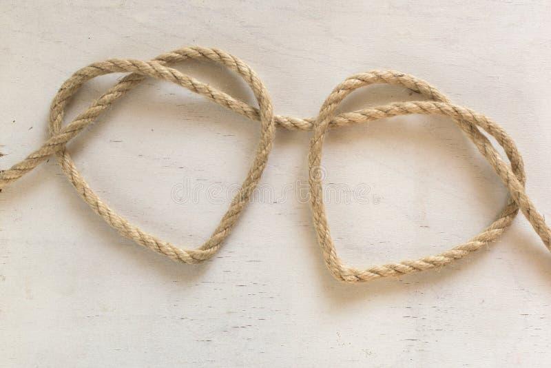 Dos cuerdas del corazón conectadas con un nudo imagenes de archivo