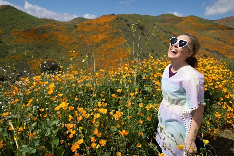 Dos ?culos de sol vestindo do cora??o da jovem mulher poses e da roupa ocasional no campo da papoila imagens de stock royalty free