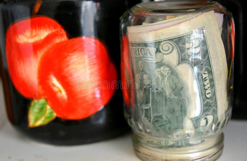 Dos d?lares de dinero en el fondo colorido de los ahorros de cristal del banco imagen de archivo