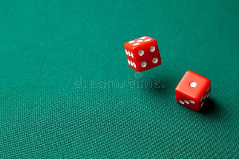 Dos dados rojos en la tabla de juego verde del póker en casino Juego en línea del concepto Copie el espacio para el texto imágenes de archivo libres de regalías