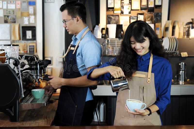 Dos de barista asiático que hace el latte o el café del cappucino en café imagenes de archivo