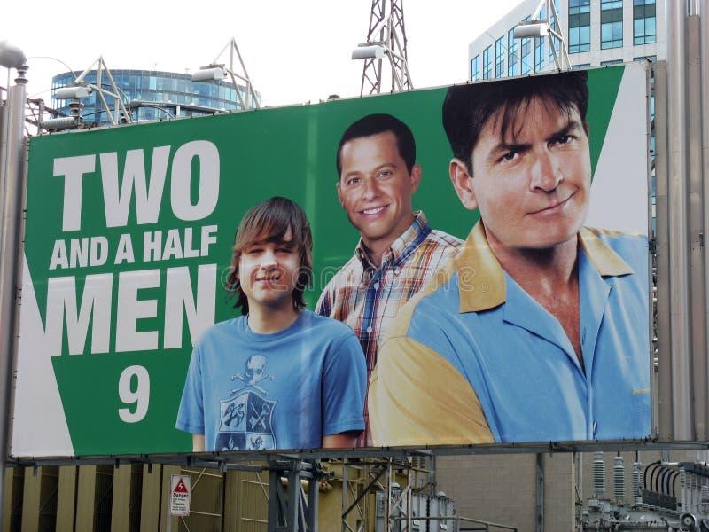 Dos de Charlie Sheen y una cartelera de los hombres de la mitad fotos de archivo