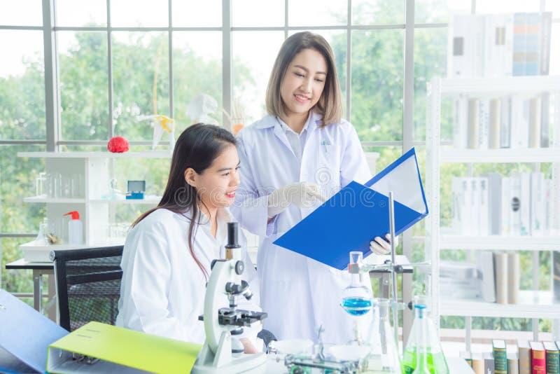 Dos de científicos en la capa blanca que trabaja en el laboratorio foto de archivo