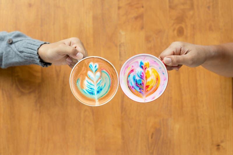 Dos de gente dan sostener la taza de café caliente del arte del Latte en café foto de archivo libre de regalías