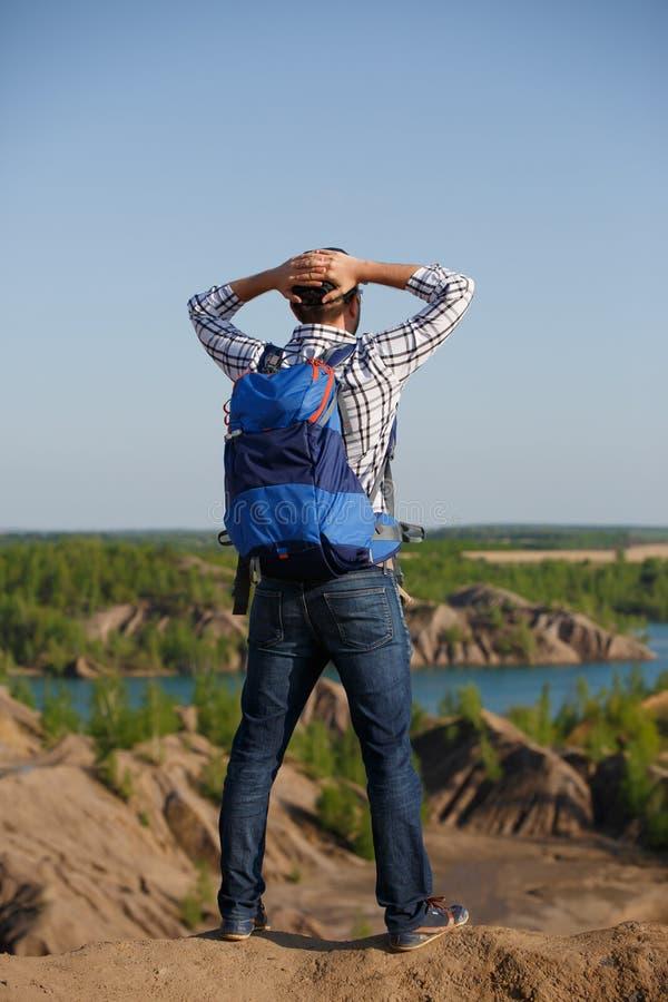 Dos de photo d'homme de touristes avec le sac à dos avec des mains derrière la tête sur la colline contre le contexte des étendue photos stock