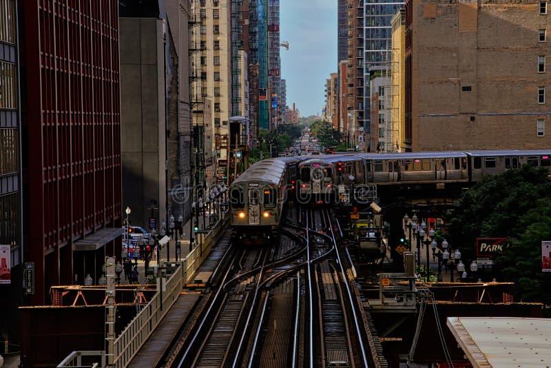 Dos del ` s de Chicago elevaron el tren del ` del EL del ` en vías sobre la ciudad, transportando a viajeros durante hora punta imagen de archivo libre de regalías