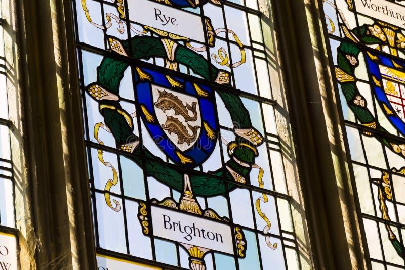 Dos delfínes en el escudo de armas de Brighton en el vitral colorido en la catedral de Chichester - iglesia de la catedral del sa fotos de archivo libres de regalías