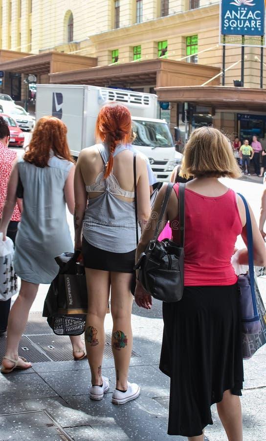 Dos des clientes de femmes avec tous leurs sacs attendant le passage piéton dedans près d'Anzac Square image stock