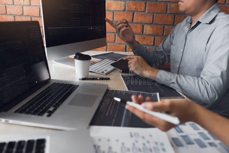Dos desarrolladores de software están analizando juntos sobre el código escrito en el programa en el ordenador fotos de archivo