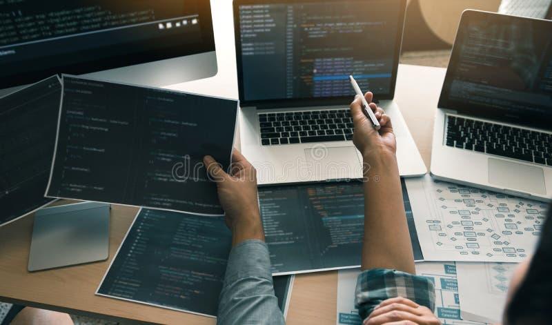 Dos desarrolladores de software est?n utilizando los ordenadores para trabajar as? como su socio en el escritorio de oficina fotografía de archivo