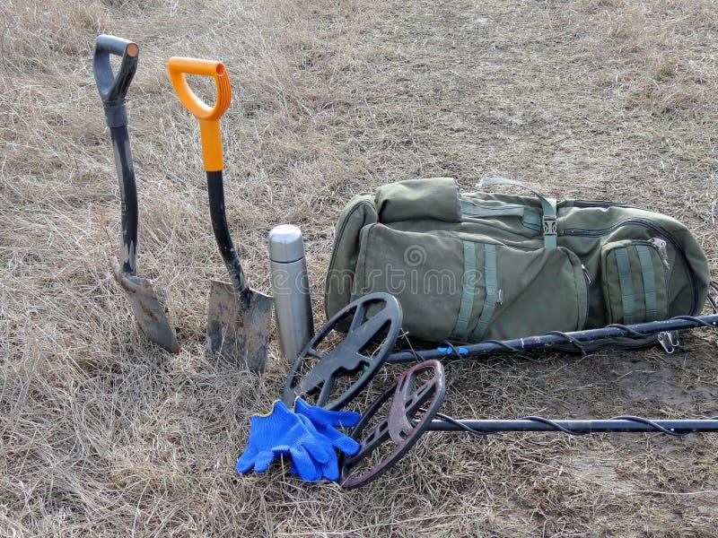 Dos detectores de metales traspalan el soporte del termo de la mochila en hierba seca fotografía de archivo