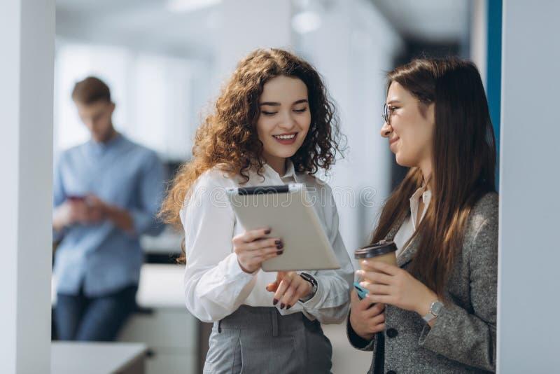 Dos directores de gerente de sexo femenino que discuten ideas del proyecto sobre la tableta digital mientras que camina abajo en  imagen de archivo libre de regalías