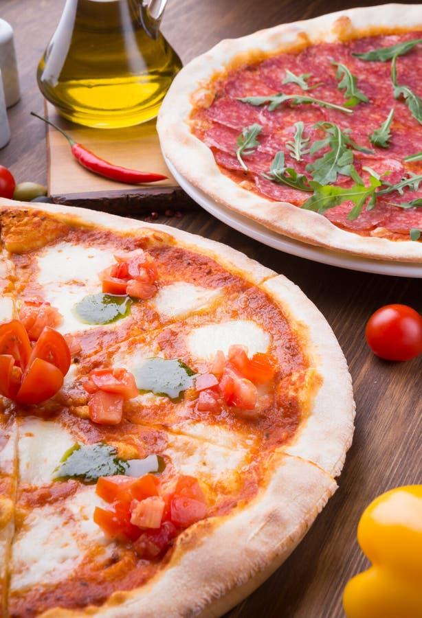 Dos diversas pizzas cocieron y sirvieron recientemente en la tabla de madera fotos de archivo
