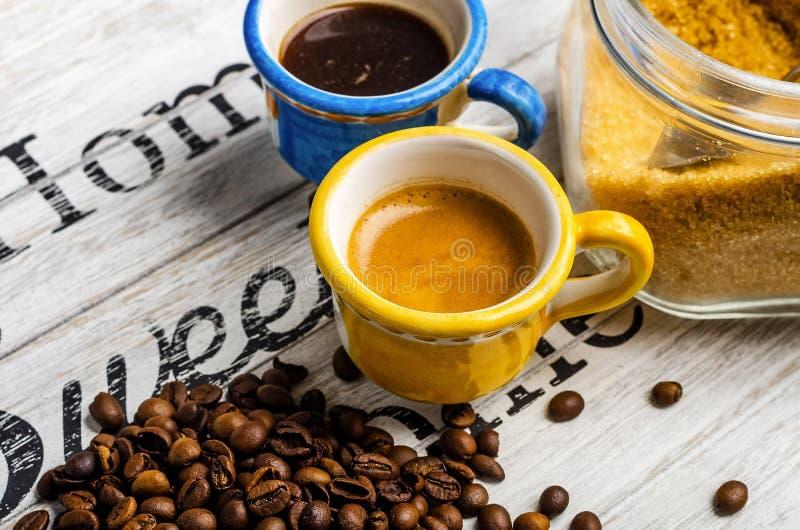 Dos diversas tazas de café y de granos de café y de azúcar de caña foto de archivo libre de regalías