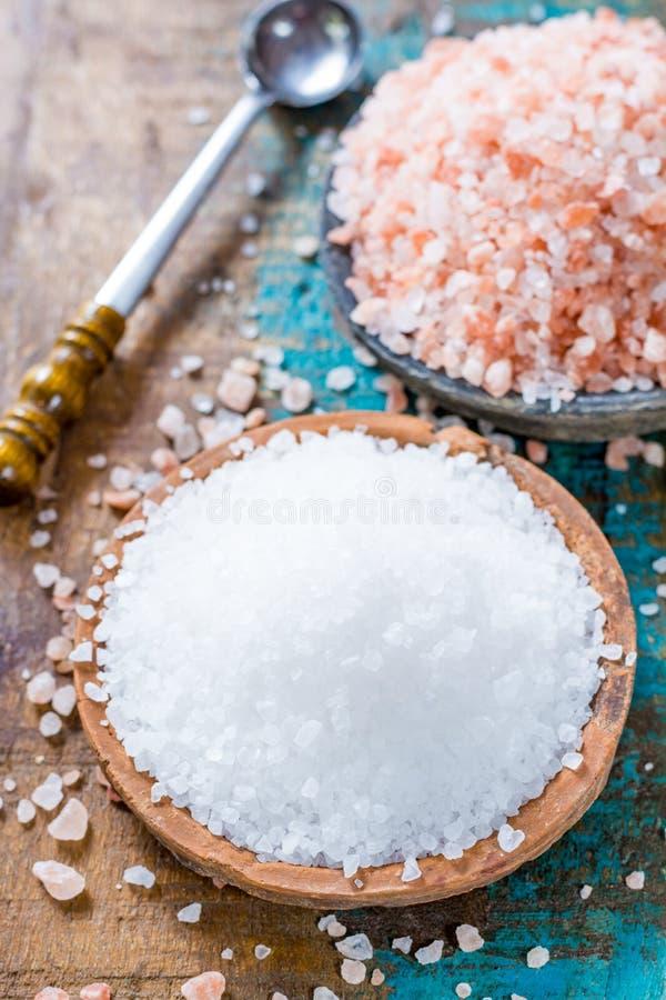 Dos diversos tipos de sal natural en los cuencos de piedra en sur de madera foto de archivo