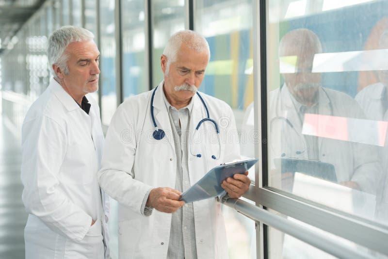 Dos doctores de sexo masculino con el tablero en el pasillo del hospital fotos de archivo libres de regalías