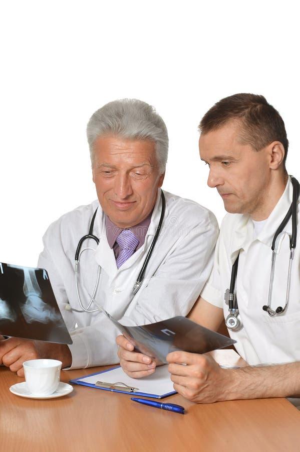 Dos doctores de sexo masculino que discuten radiografías foto de archivo