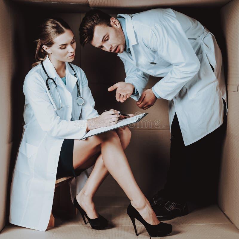 Dos doctores jovenes en las capas blancas en caja de cartón fotos de archivo