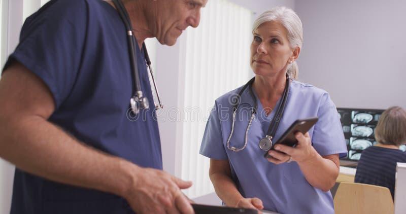 Dos doctores o enfermeras maduros caucásicos en los dispositivos de la tecnología fotos de archivo libres de regalías