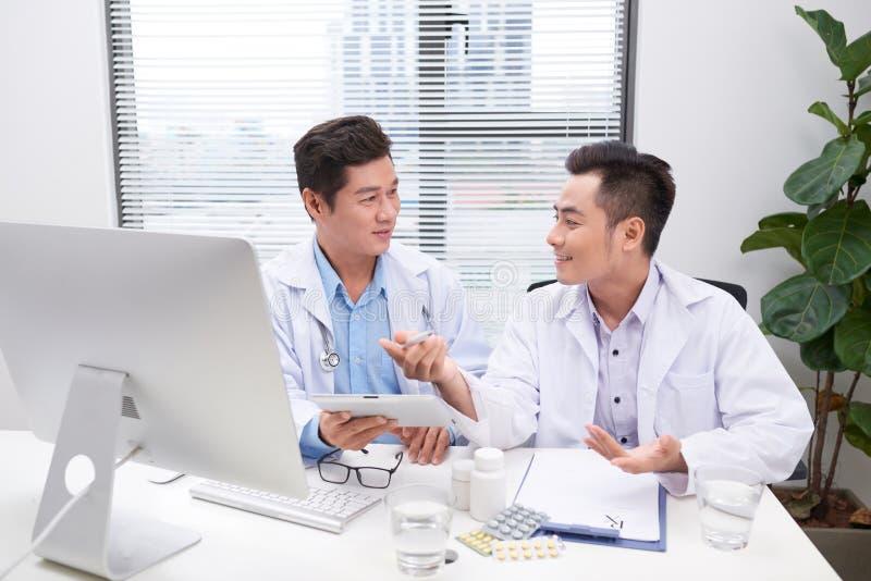 Dos doctores que detienen y que hablan del paciente en oficina imagen de archivo
