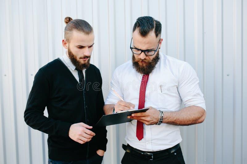 Dos documentos de firma del hombre de negocios barbudo imágenes de archivo libres de regalías