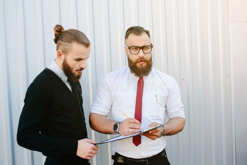 Dos documentos de firma del hombre de negocios barbudo fotos de archivo