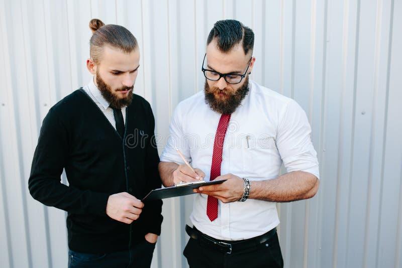Dos documentos de firma del hombre de negocios barbudo imagenes de archivo