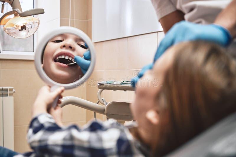 Dos doutores cuidado sempre Menina no escrit?rio dental, olhando no espelho Cl?nica moderna imagens de stock