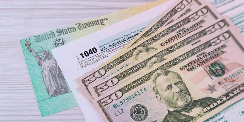 Dos E.U. do imposto federal da renda um formulário 1040 de imposto com dinheiro e verificação de reembolso fotos de stock royalty free