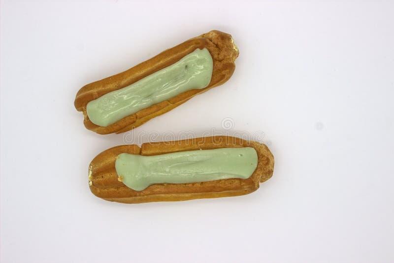 Dos Eclairs deliciosos del pistacho Una imagen aislada en el fondo blanco imágenes de archivo libres de regalías