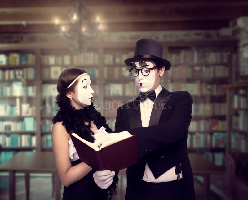 Dos ejecutantes del teatro de la pantomima que presentan con el libro imagen de archivo libre de regalías