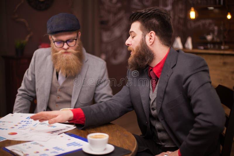 Dos ejecutivos felices que se encuentran en una cafetería y que tienen una conversación del negocio imágenes de archivo libres de regalías