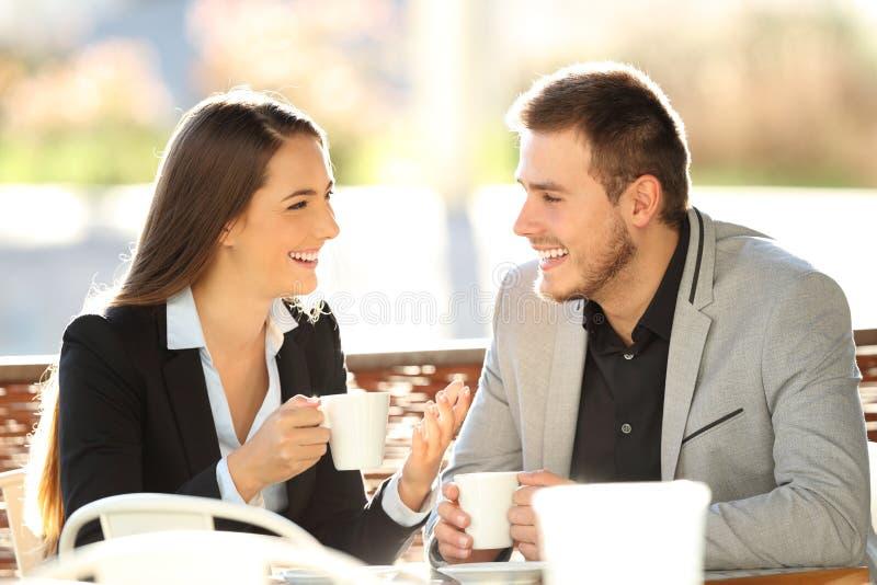 Dos ejecutivos que hablan durante un cofee adaptan una barra foto de archivo libre de regalías