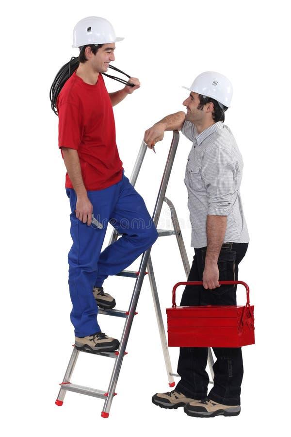 Dos electricistas que tienen en la charla imagen de archivo libre de regalías