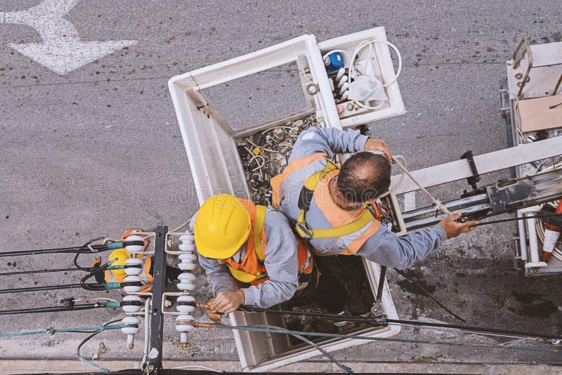 Dos electricistas que trabajan con los alambres imagen de archivo