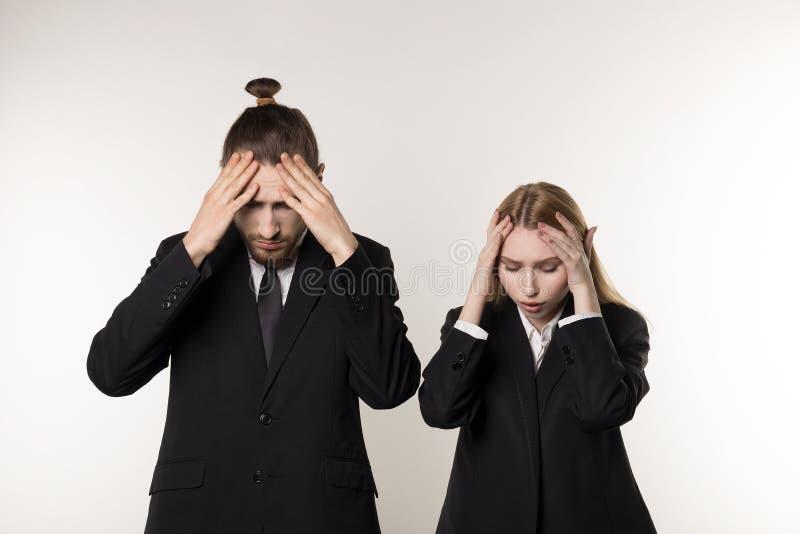 Dos empleados jovenes en los trajes negros que se colocan con las manos en la cabeza, trabajadores despedidos después de la quieb imagen de archivo libre de regalías
