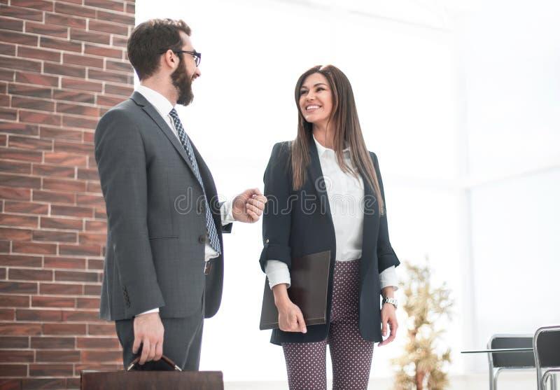Dos empleados que hablan la colocaci?n en la oficina fotos de archivo
