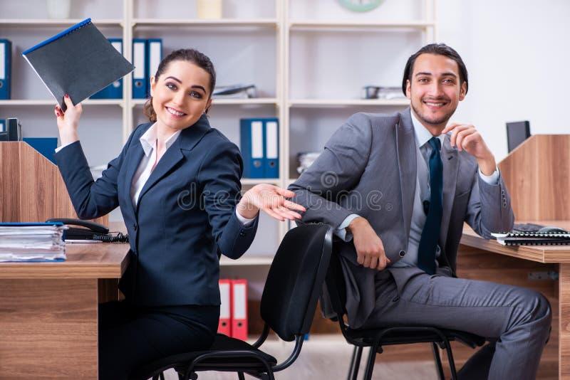 Dos empleados que trabajan en la oficina imagen de archivo