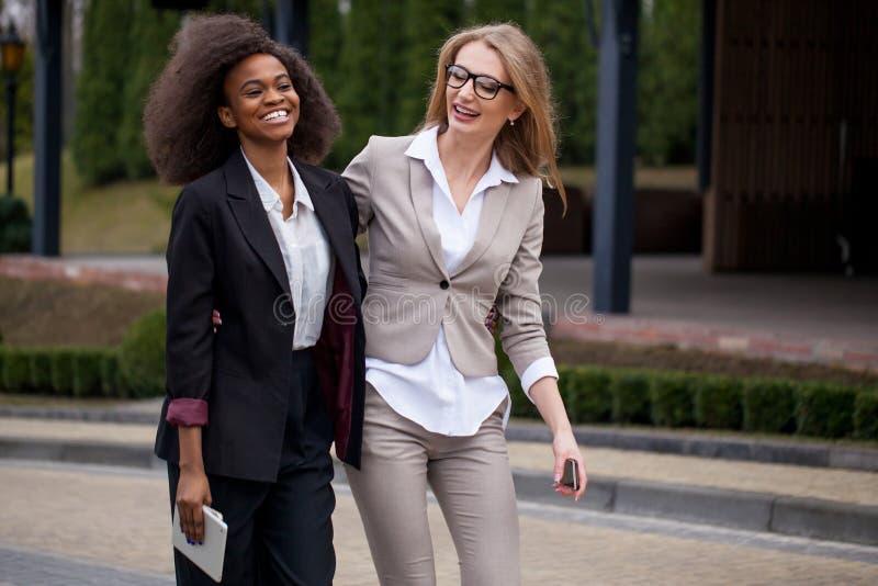Dos empresarias bastante africanas y caucásicas alegres en trajes elegantes están caminando a lo largo del parque fotos de archivo libres de regalías
