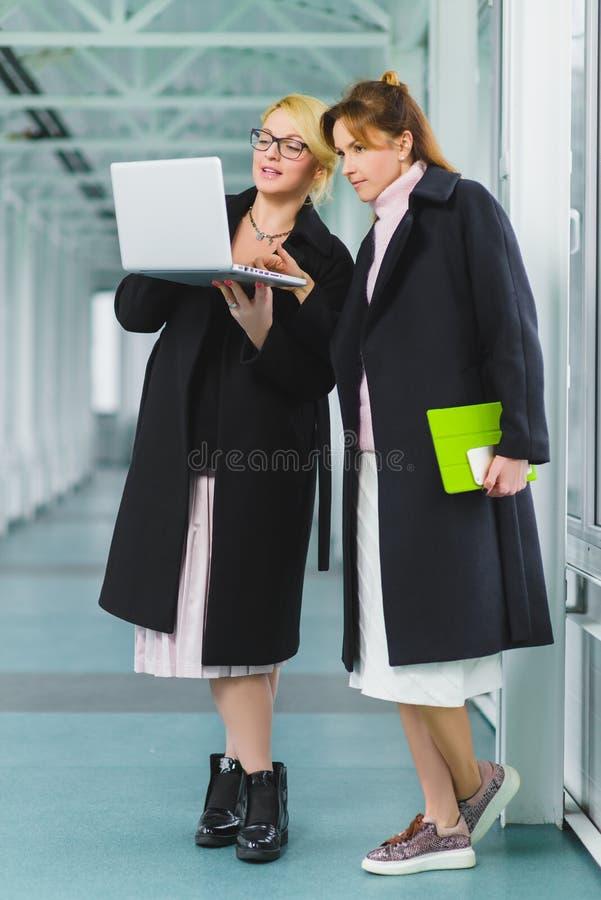 Dos empresarias elegantes que trabajan junto en un proyecto en el pasillo imágenes de archivo libres de regalías