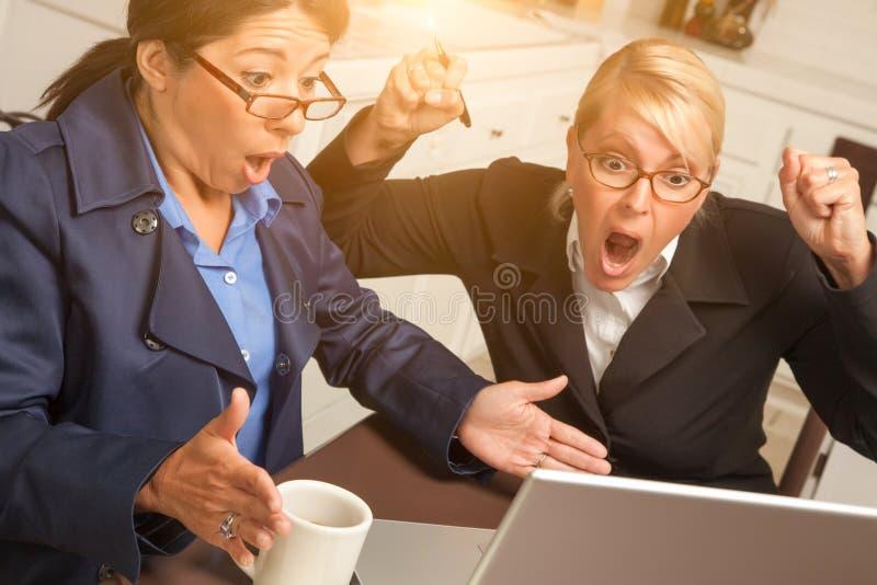 Dos empresarias emocionadas celebran éxito en el ordenador portátil fotos de archivo
