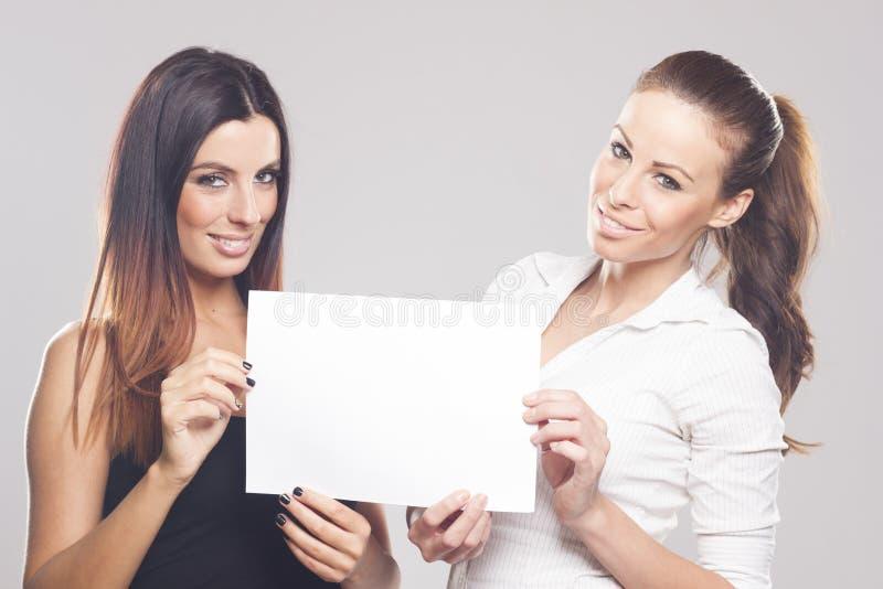 Dos empresarias hermosas que muestran la muestra vacía imágenes de archivo libres de regalías