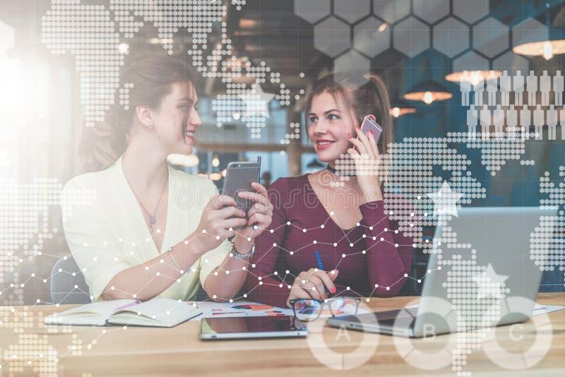 Dos empresarias jovenes se están sentando en la tabla La primera muchacha está sosteniendo el smartphone, segundo está hablando e fotos de archivo