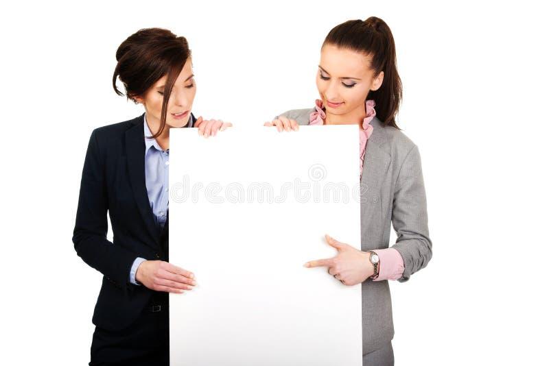 Dos empresarias que llevan a un tablero blanco grande imagenes de archivo