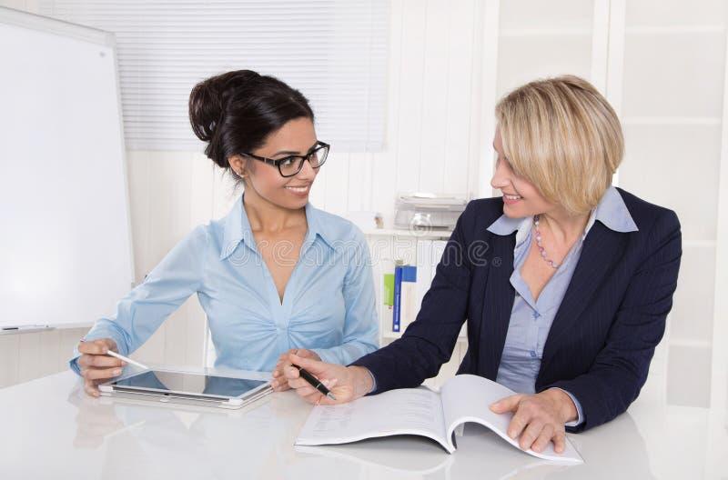Dos empresarias que trabajan junto en el escritorio en la oficina. fotografía de archivo
