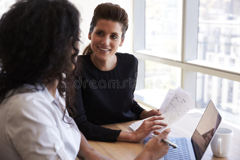 Dos empresarias que usan el ordenador portátil en la reunión de la oficina imagenes de archivo