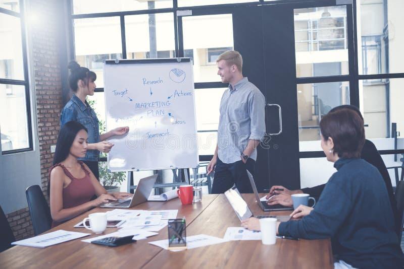Dos empresarios confiados que ofrecen una presentación en pizarra con colegas multiétnicos de compañeros de trabajo, Teamwork fotos de archivo