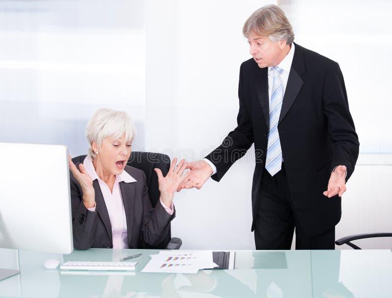 Dos empresarios que discuten con uno a foto de archivo